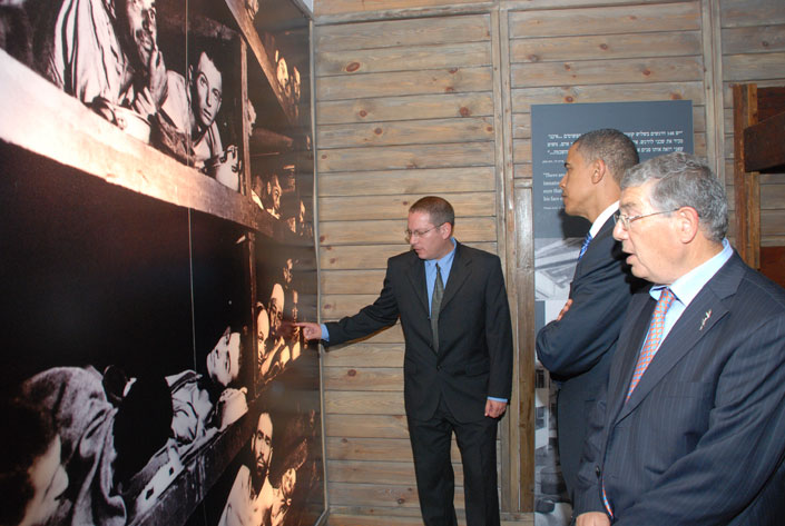 Senator Obama studies a photograph of the liberation of Buchenwald in the Holocaust History Museum; Senior Guide Guy Shemer is pointing at Holocaust survivor Elie Wiesel who appears in the image