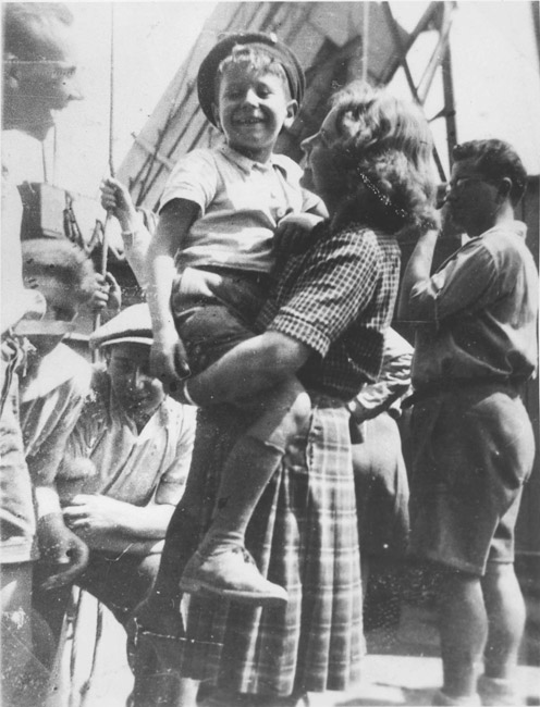 Children from Buchenwald on the ship to the Land of Israel. Lolek is held by the counselor