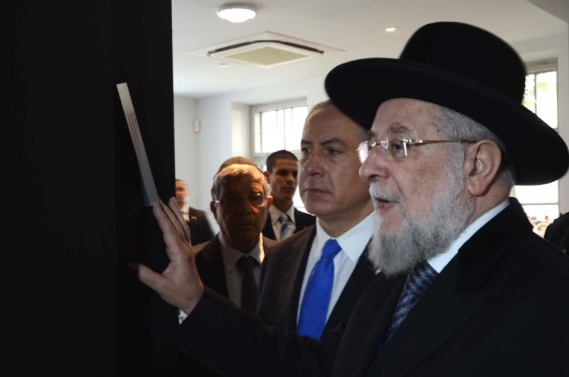 Rabbi Lau, Chairman of the Yad Vashem Council, affixing a mezuzah at the entrance to the exhibition
