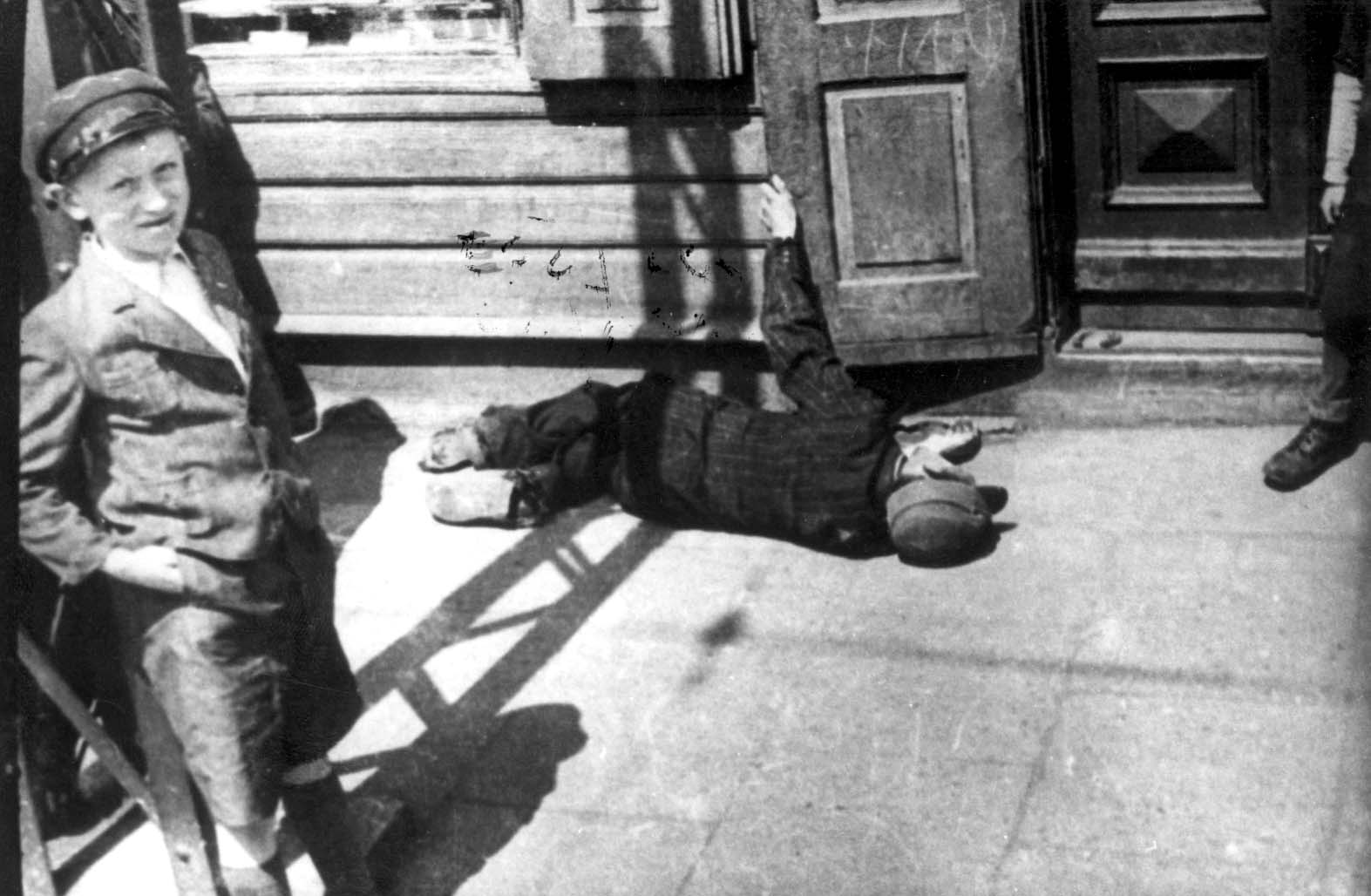 Lodz, Poland, A child standing next to an exhausted man lying in the street