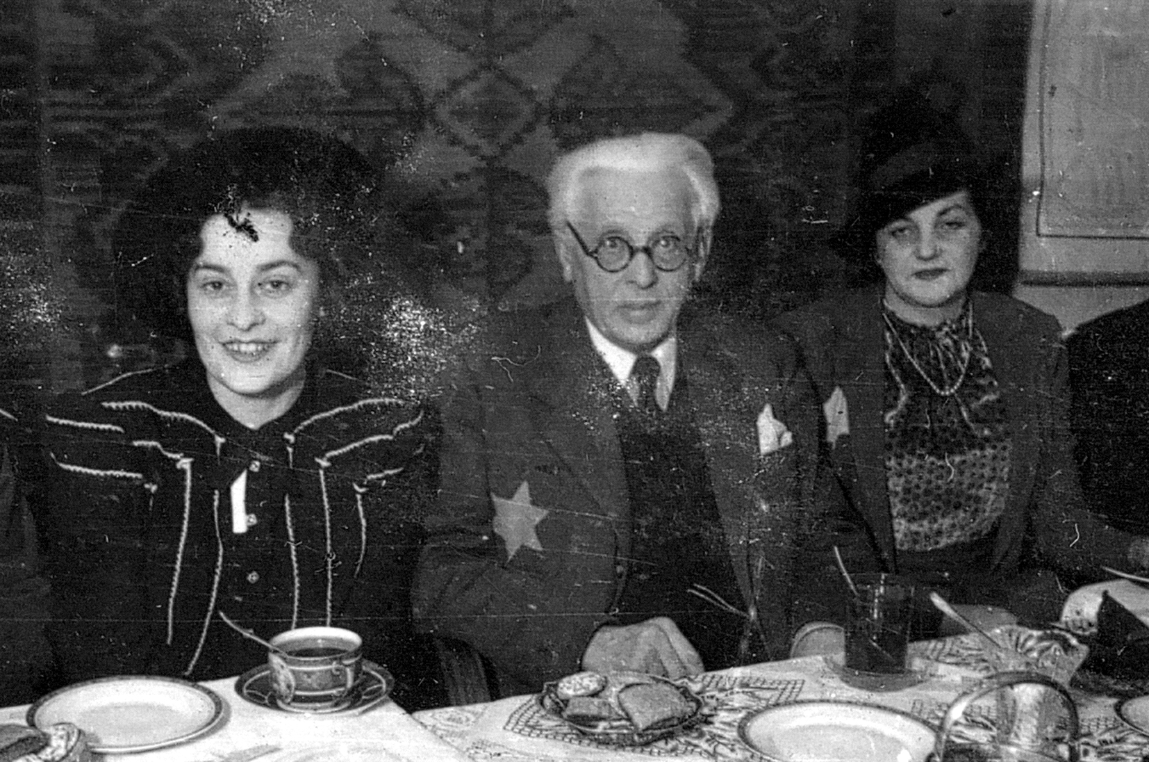 Lodz, Poland, Chairman of the Judenrat Rumkowski, his wife Regina to his left, his brother's wife Helena to his right, at an event in the ghetto