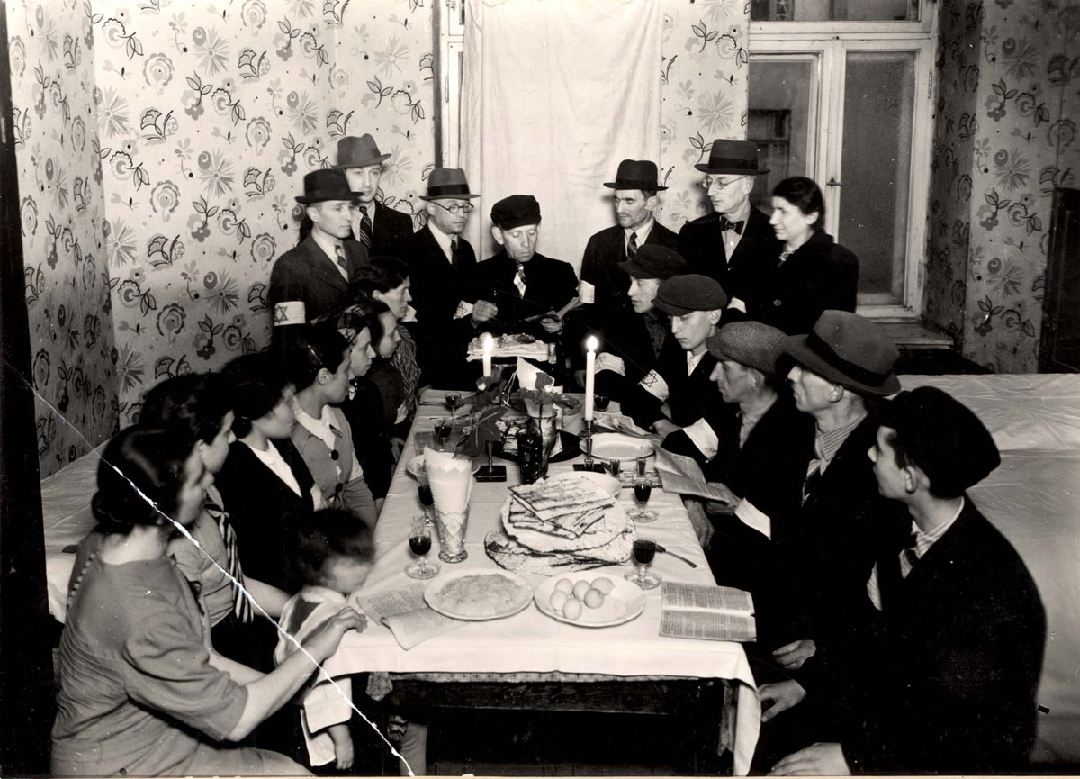 Warsaw, Poland, Jews around a seder table in the ghetto, reading from the Passover Haggada