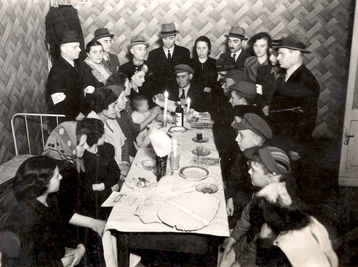 Warsaw Ghetto, Poland, People sitting at the Sabbath table. Shabbat candles are on the table.