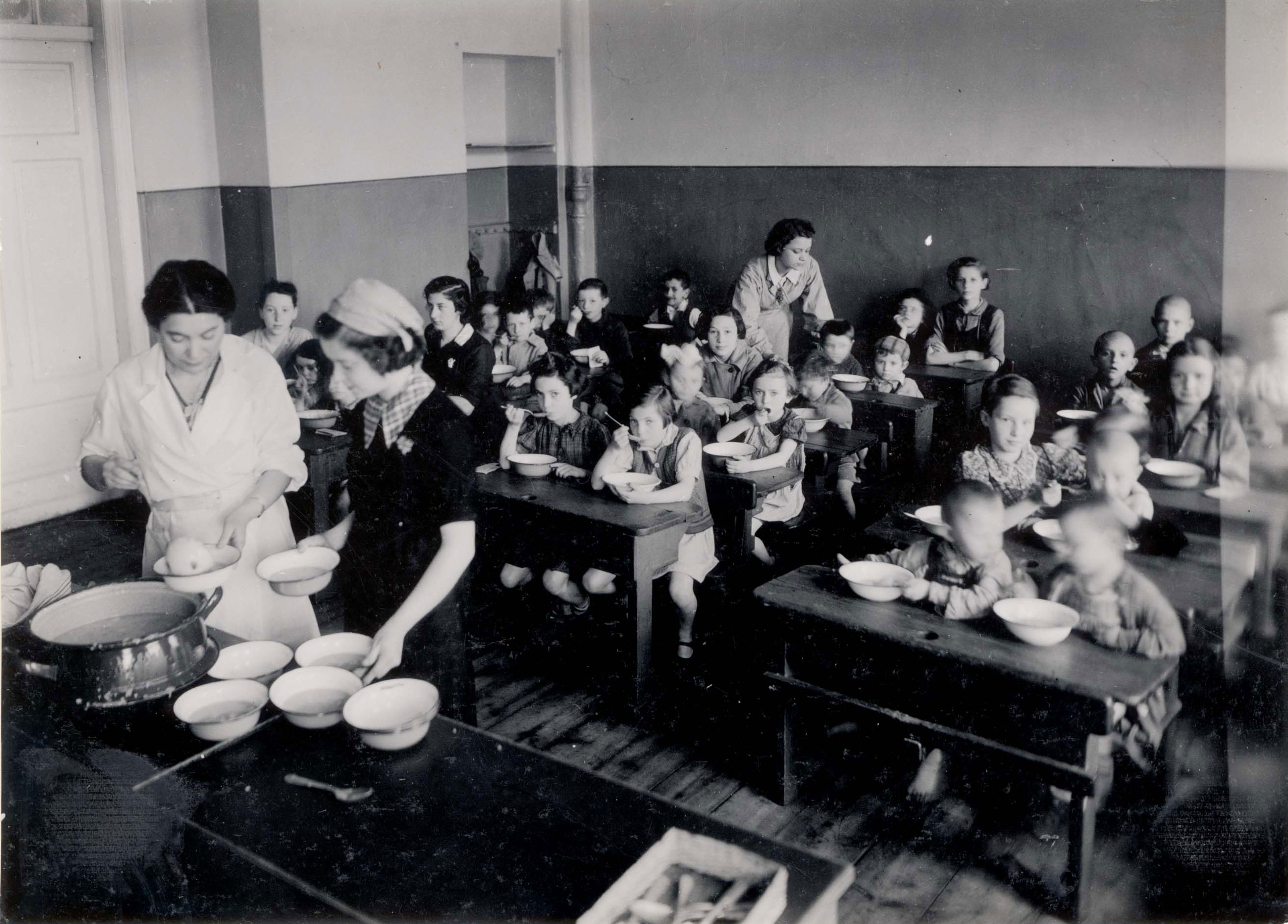 Warsaw, Poland, Women distributi​ng food to children in a public soup kitchen in the ghetto