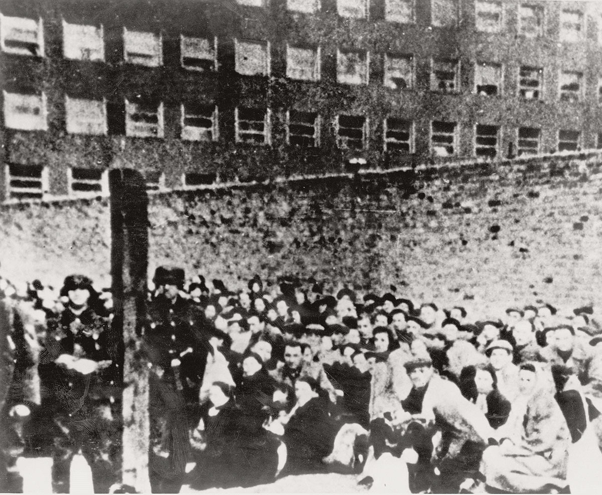Jews crowded together under German guard at the Umschlagplatz, the collection point in the Warsaw ghetto, prior to their deportation to the death camps, spring 1943