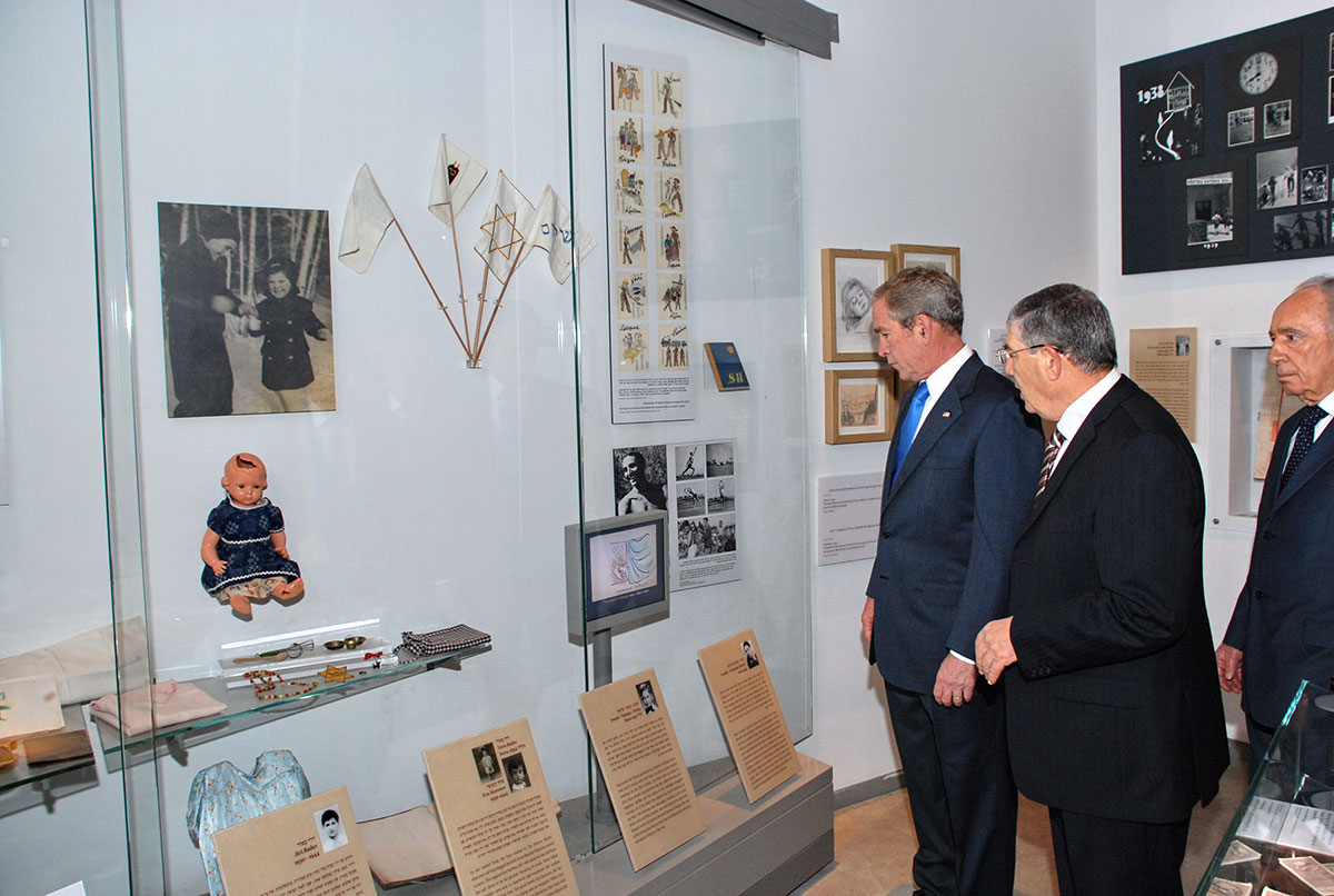 President Bush, guided by Chairman of the Yad Vashem Directorate Avner Shalev and accompanied by President Shimon Peres, studies an exhibit in the Holocaust History Museum