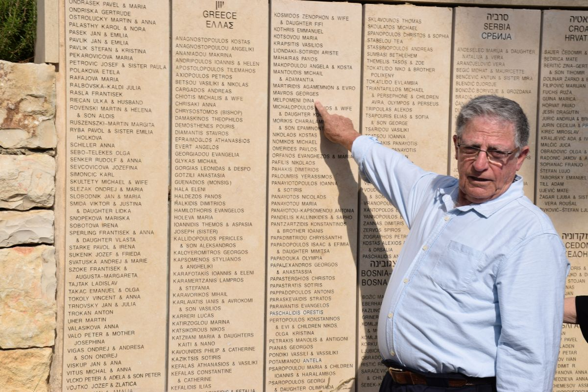Yossi Mor pointing to Melpomeni Dina's name, inscribed on the Wall of Honor in the Garden of the Righteous Among the Nations at Yad Vashem