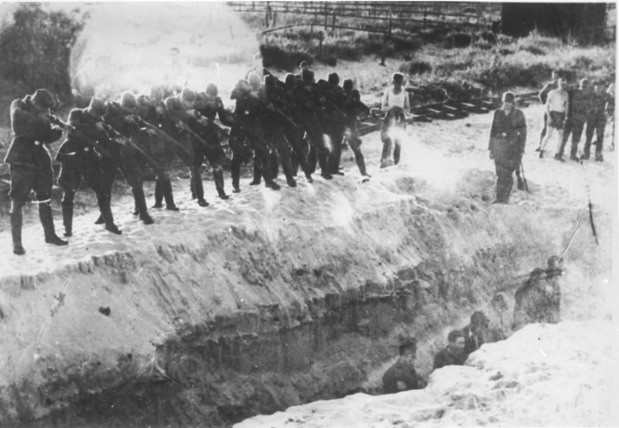 Einsatzgruppen soldiers shooting Jews who are in a ditch