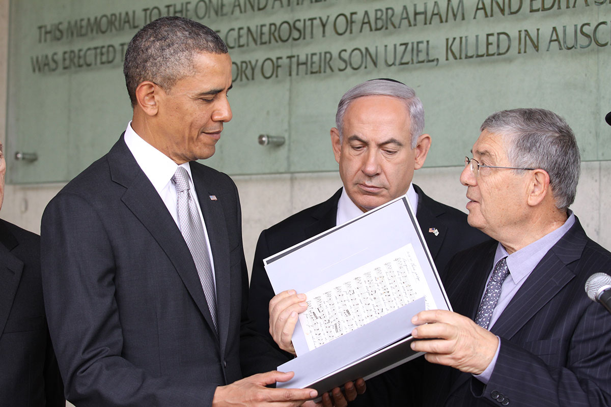 President Barack Obama looking at a facsimile of a Holocaust era manuscript presented to him by Chairman of the Yad Vashem Directorate Avner Shalev as Prime Minister Netanyahu looks on