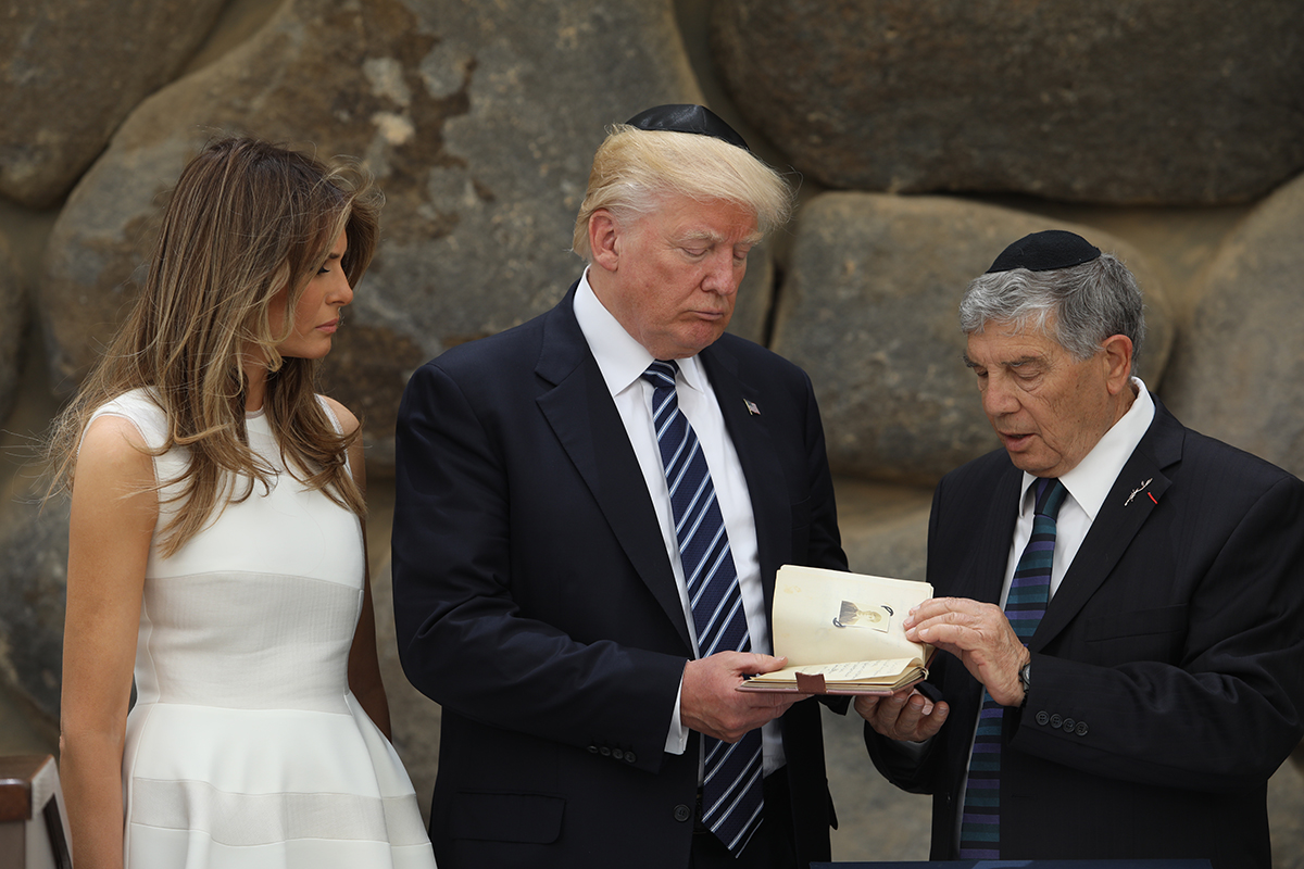 President Donald J. Trump and First Lady Melania Trump look through the replica of a Holocaust-era album.