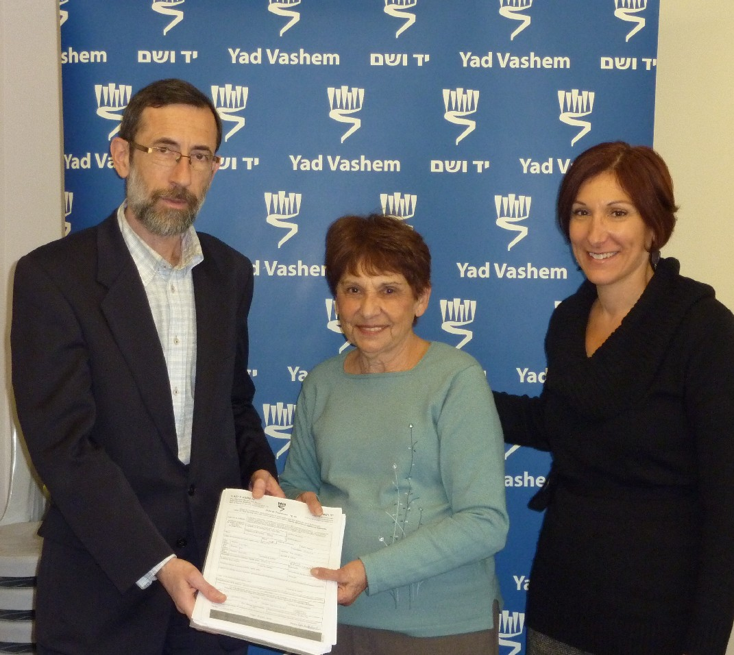 Alexander Avram (Left), director of the Hall of Names, and Cynthia Wroclawski (Right), Manager of the Shoah Victims' Names Recovery Project, receive Pages of Testimony from Amalia Miodownik (center)