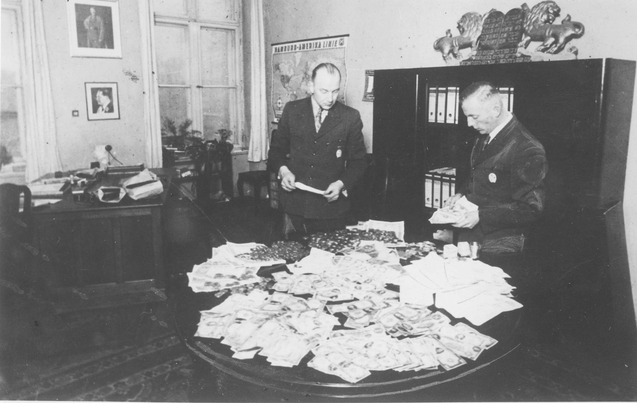 Lodz, Poland. Hans Biebow (right) and Erik Tschemulla counting American dollars in the office in the ghetto