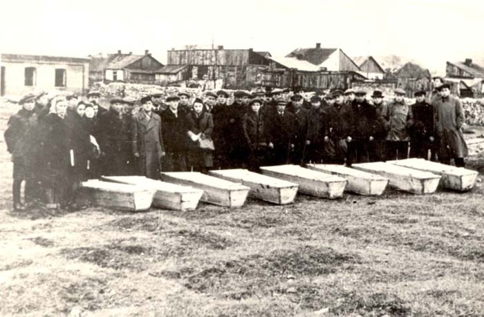Mourners standing behind the coffins of pogrom victims, Kielce, Poland, 1945