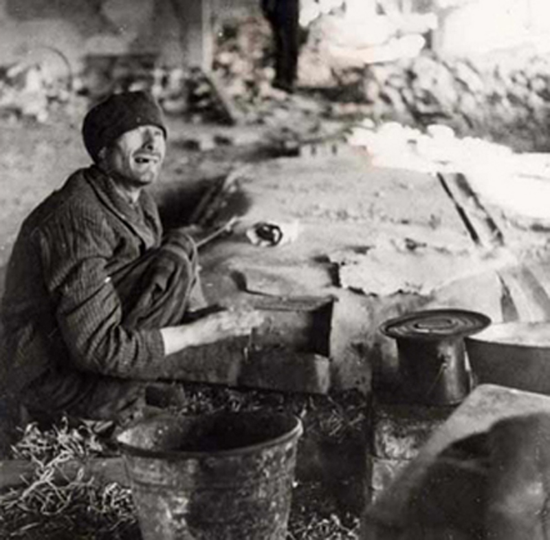 A survivor sits near a pot of potatoes at the Dora-Mittelbau Concentration Camp in Germany