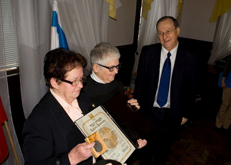 Zofia Grocholski receives a medal and a certificate from the Israeli Ambassador to Poland, Zvi Rav-Ner. Next to her is Sally Frishberg, who pressed for Mr. Grocholski's acknowledgment as Righteous Among the Nations.