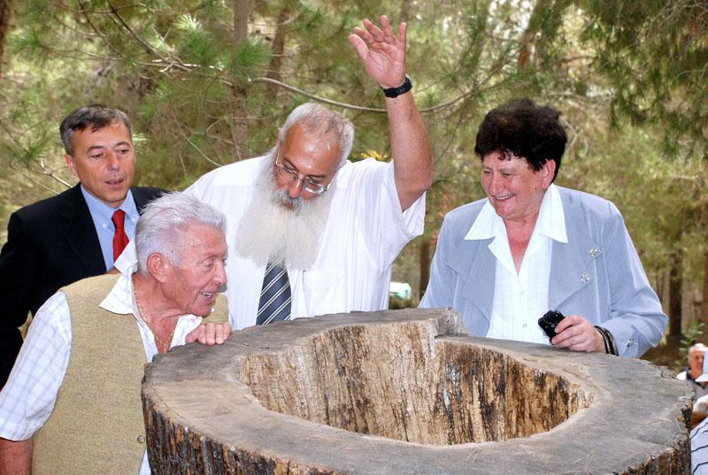 Jakob Silberstein (second from left) looks at the hollow tree trunk inside which he hid.