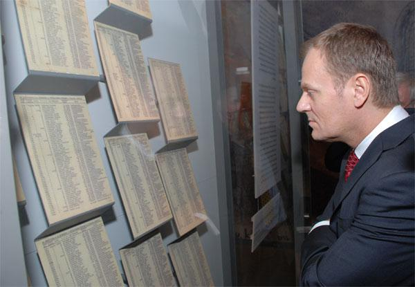 """Prime Minister Tusk studies a display of """"Schindler's List"""" during his visit of the Holocaust History Museum"""