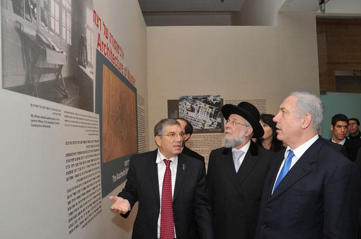 Chairman of the Yad Vashem Directorate Avner Shalev explains a display in the exhibition to Prime Minister Netanyahu as Chairman of the Yad Vashem Council Rabbi Israel Meir Lau looks on