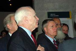 Senators John McCain (forefront) and Lindsey Graham study an exhibit in the Holocaust History Museum