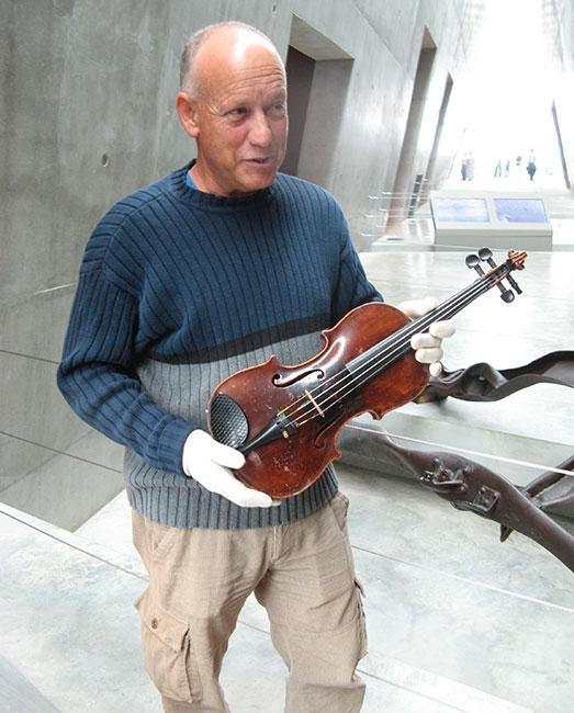 Seffi Hanegbi inside the Holocaust History Museum holding the violin he donated that had belonged to the partisan Mottele