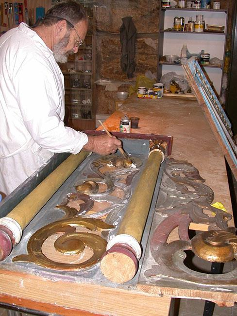 Conservator Eliyahu Matzkin restoring a detail on the façade of a Torah Ark from a synagogue in Hârlău, Romania, in preparation for its display in the Yad Vashem Synagogue, June 2005