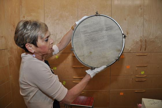 Haviva displays a drum made from a desecrated Torah scroll, part of the Yad Vashem Artifacts Collection