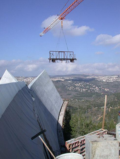 Frame of a railcar that was used to deport Belgian Jews to the death camps in Poland, being lowered into the new Holocaust History Museum at Yad Vashem through the unfinished roof of the building