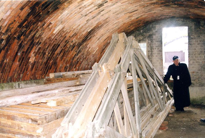 The A-frame from the wooden roof of a prison barrack in Kaufering concentration camp shown in storage inside the circular buildings that housed prisoners. Winter 2003