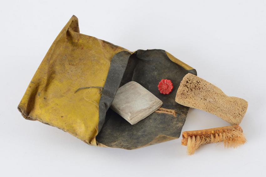 A cloth bag containing soap, a sponge, a toothbrush, a button and a tiny piece of lipstick wrapped in paper