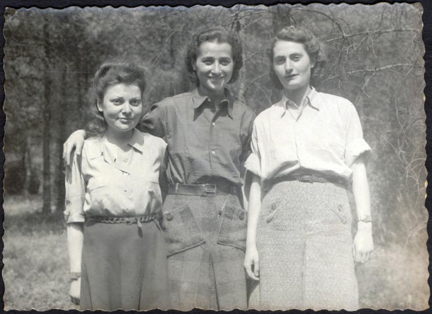 """Hilde Grünbaum (right) in Bergen-Belsen, one month after the liberation on 15 April 1945, with her friends from the women's orchestra in Auschwitz – cellist Anita Lasker Walfisch (center), and violinist """"Little Helen""""(left), May 1945"""