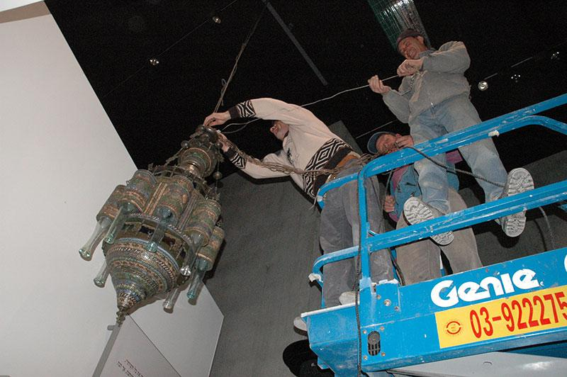 A synagogue lamp from North Africa that was looted by the Nazis, being secured in place in the gallery depicting the fate of the Jews of North Africa during the Holocaust. February 2005
