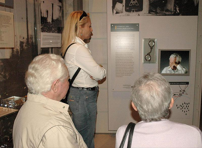 """Shimon Srebernik z""""l, a survivor of the Chelmno death camp, viewing his testimony on a screen displayed next to the leg manacles he was forced to wear as a prisoner, at the opening of the new Holocaust History Museum, Yad Vashem 2005"""