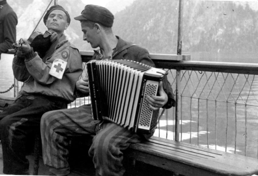 Ebensee, Austria, a US army medic and a liberated inmate playing the violin and accordion
