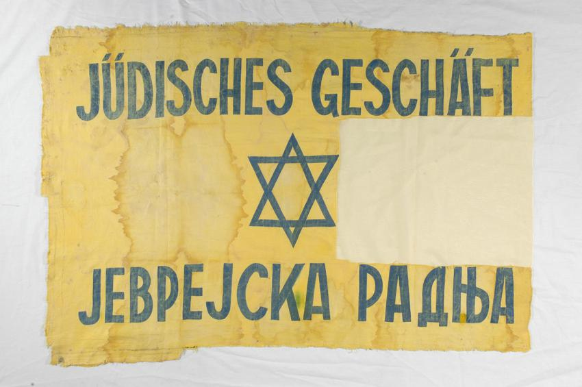 Cloth sign printed in Serbo-Croat and German, announcing that the business is in Jewish hands. The Akons family were forced to hang the sign in the window of their store in Belgrade, Yugoslavia
