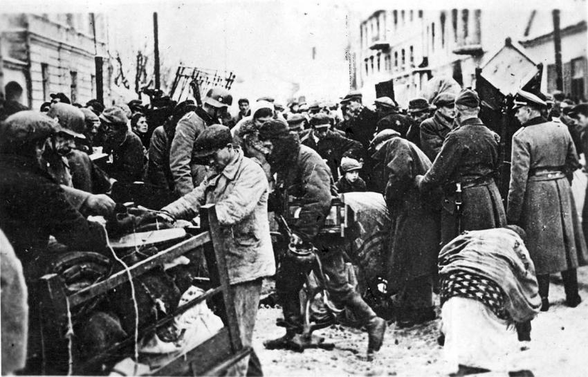 Policemen guarding Jews who are being relocated into the ghetto in Grodno, Poland, November 1941