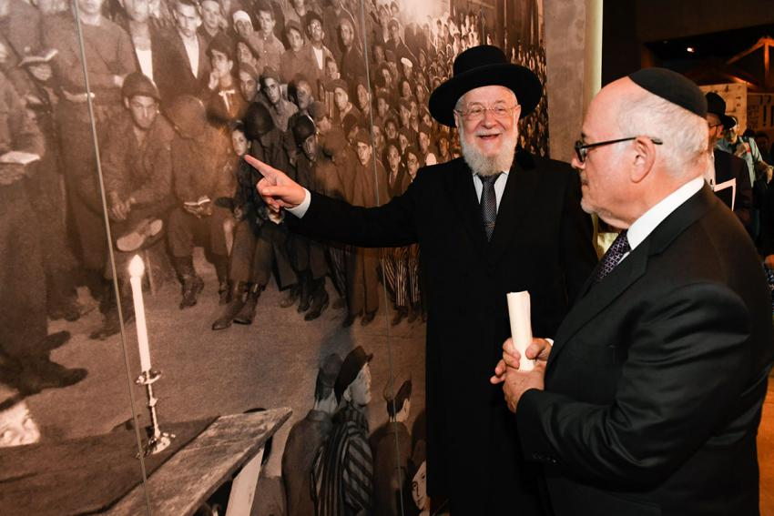 Yad Vashem Council Chairman Rabbi Israel Meir Lau (left) points to himself as a young boy in a photograph of a liberation ceremony at Buchenwald, displayed in Yad Vashem's Holocaust History Museum