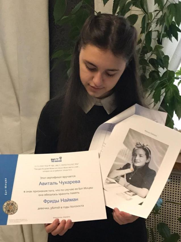 """Avital from St. Petersburg, holding her certificate and the photograph of her """"twin"""""""