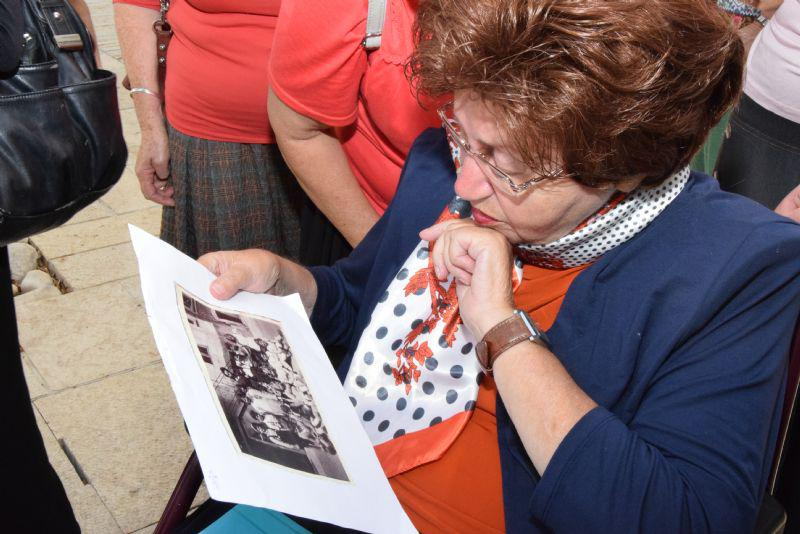 Survivor Tova Silverstein looks at a photo of herself, her sister Matylda and other children at the postwar children's home in Marquain, Belgium. Her father, Hersch Lowenbraun, stands in the background - he was one of the children's teachers at the home