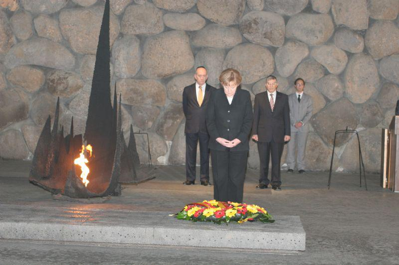 German Chancellor Dr. Angela Merkel lays a wreath in the Hall of Remembrance. To the Chancellor's left is Prime Minister Ehud Olmert and to her right is the Chairman of the Yad Vashem Directorate Avner Shalev
