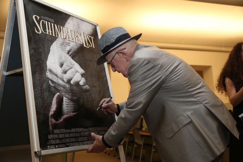 """Branko Lustig autographing a poster from the epic Holocaust film """"Schindler's List"""" on display at Yad Vashem"""