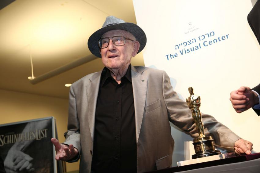 Branko Lustig standing next to the Oscar he won for producing Schindler's List which is now on display in Yad Vashem's Visual Center in Jerusalem