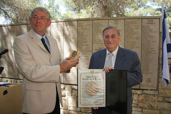 Henk Brink accepts the certificate and medal of honor of Righteous Among the Nations on behalf of his late father Henk Drogt from the Chairman of the Commission for the Designation of the Righteous Among the Nations, Supreme Court Justice Yaacov Turkel