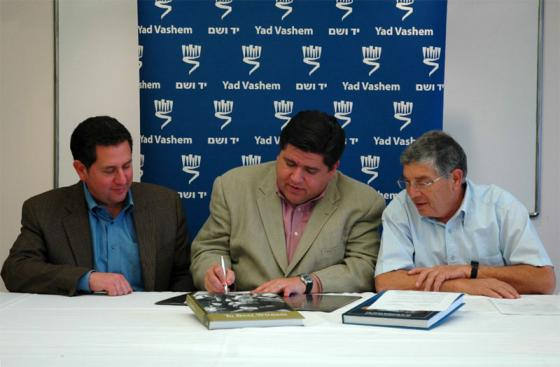 JB Pritzker (c) signs the agreement as Yad Vashem Chairman Avner Shalev (r) and Illinios Holocaust Museum Executive Director Richard Hirschhaut (l) look on
