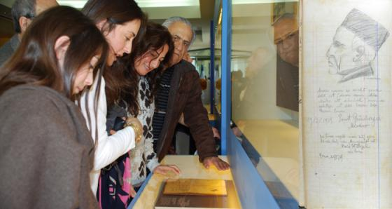 Eldad Labi and members of his family looking at the guest book from his father Eliyahu Pines Kosher guesthouse in Rome.