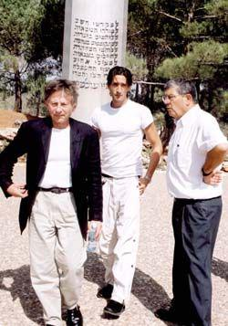 Roman Polanski (left in black jacket) accompanied by Avner Shalev (right) and Adrian Brody (center) as they stand in front of the Pillar of Heroism