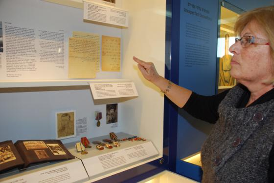 Bracha Kluzny pointing at the letter that her mother Chava sent her brother Yitzhak Tunik in Eretz Israel at the end of the war, relating the tragic fate of their family.