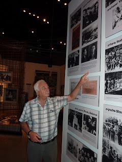 Daniel Lerner, near a photograph of his father, Baruch (Boria) Lerner, in the Holocaust History Museum at Yad Vashem
