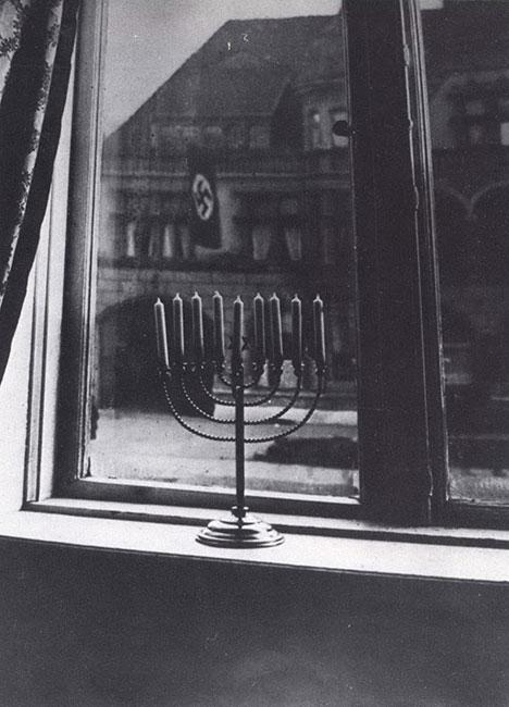 A photograph taken in 1932 by Rachel, wife of Rabbi Akiva Posner, of their candle-lit Hanukkah menorah against the backdrop of the Nazi flags flying from the building across from their home in Kiel Germany