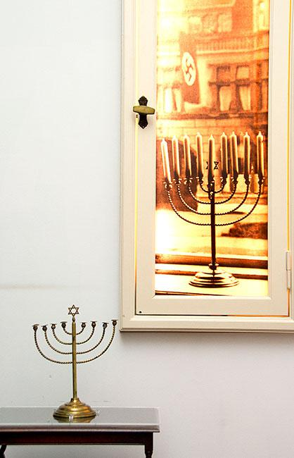 The Posner family Hanukkah menorah displayed in the Holocaust History Museum at Yad Vashem beside the photograph that was taken in the Posner family home in Kiel on their last Hanukkah in Germany, 1932
