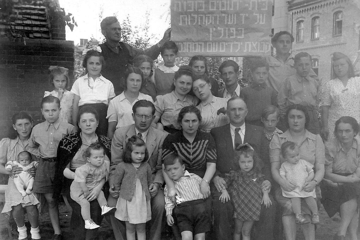 Dr. Nechama Geller, Director of the children's home in Zabrze (seated center), together with the children and staff in front of the children's home. Zabrze, Poland, postwar